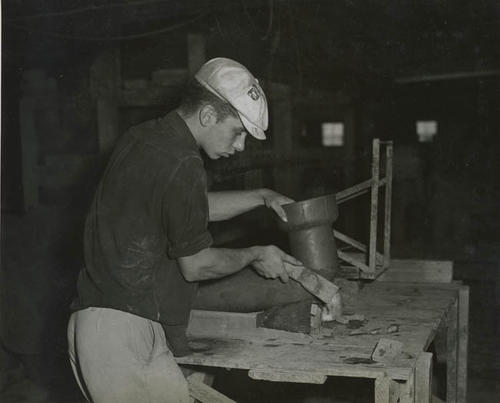 Young man, Ronald Poelstra, working on a clay pipe.