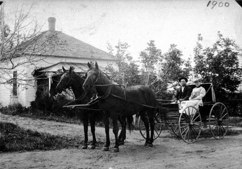 Mr. and Mrs. A.J. Ware posing with their carriage and two horses in front of a Corona home. The wife's first name was Florence.