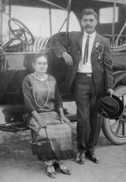 Photo of a couple on a car.  Marciana Pegero Rojo and Mr. Pegero.  They are Amelia Lerma's paternal grandparents.