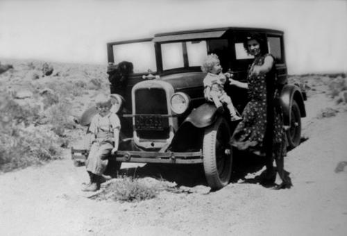 Florence A. Knorr (mother) and Melvin Knorr (baby) and Charles Knorr (toddler) in the Mohave Desert near Barstow. The family is standing by a black car.