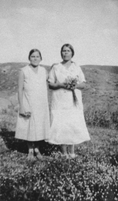 Maria Macial (right) and Rufina Acevedo (left) standing in a field.