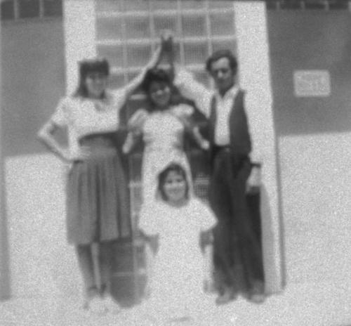 Family shot of four people posed in front of a doorway.