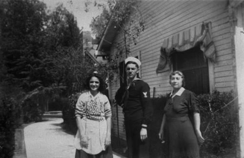 Ruth, Julio and Mrs. Lena Panattoni.  Taken at the Panattoni residence at 1006 E. 6th Street in the driveway. Looking north toward 6th street and City Park in 1943.  Julio Panattoni is dressed in a sailor uniform.
