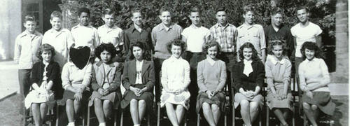 Class photo of Corona Jr. High class.  The face of the second girl from the left is cut out.