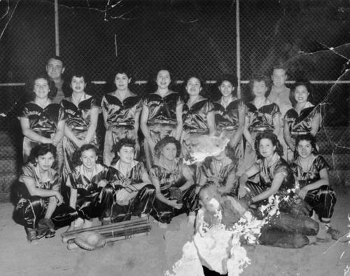 "Corona girls softball team at City Park on Sixth Street. According to Margaret Vasquez, ""They were in first place, played in Orange and San Bernardino counties and those teams were afraid to play them because they were so good. The team was given trophies too.""  Back Row, L-R: Coach Ragsdale, Norma Deleo, Margaret Zarate, Angie Flores, Dora Mendoza, Annie Bravo, Socorro ""Butch"" Garcia, Ramona Galvan, Coach, Dora. Front Row, L-R: Ruth Martinez, Gloria Medoza, Yolanda Bravo, Annie Hernandez, Whia, Katherine Delgadilla, and bat boy."