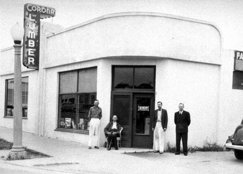 Howard Ware; A.J. Ware; Frank Ware; and a salesman are the men standing in front of the Corona Lumber, located on 4th and Main Street.