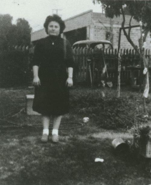 Ann Adamo in backyard. Across the fence in the background you can see the auto repair shop which is in the location at the present Ramona Tire Company.  The view of the photo is 314 West Sixth Street.