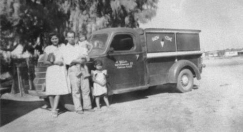 Henry and Eve Valles with two children standing by a snowone truck.  This was the first ice cream truck in Corona.