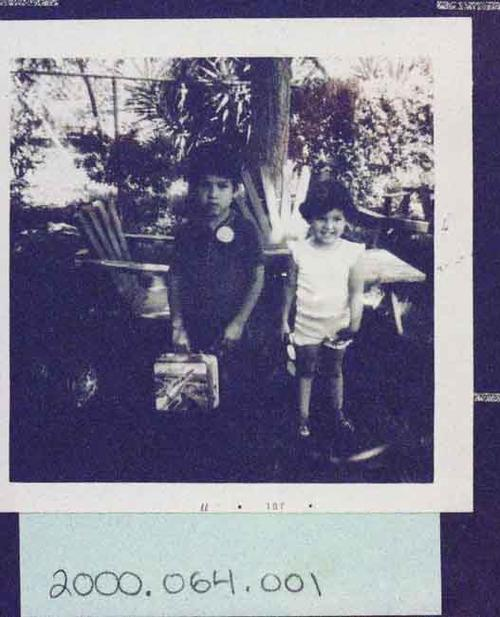 Young boy with lunchbox and young girl outside in a yard. Irene Navarro's family circa July 1977.