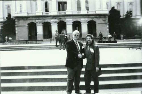 Jeff Luscher, Santiago Senior High School Math Department Chair, on the steps of Capitol Hill in Sacramento, California with Santiago Senior High School principal, Steve Kennedy.  The two men are shaking hands.