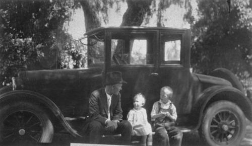 Robert Willits with children, Nancy and Ned Willits, sitting in front of a black car.