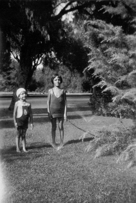 June and Ruth Panattoni cooling off in the front yard of their home at 1006 East 6th Street (previously 756). City Park in the background.