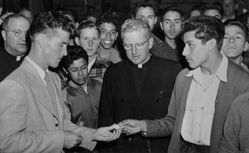 Monsignor Thompson with Corona Parks and Recreations Director giving prizes. Young boy, Brigido Ramirez. Boy above Ramirez, Jimmy Stark. Monsignor Thompson in center. Fred Montejano on the right facing left with hand outstretched.  Buddy Martinez is the man on far right with face over Montejano's left shoulder.