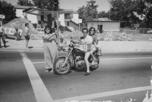 Esther Varela, John Lipari, Debra Lipari pictured with a motorcycle on a street.