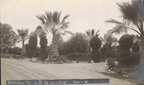 A black and white photograph postcard of the entrance driveway to the home of L.R. Nichols.