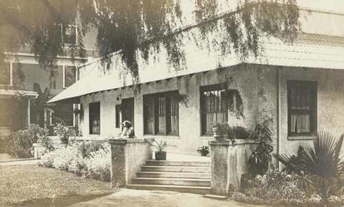 "Black and white photograph postcard of ""Maud and Walter's"" home.  Note on back of postcad reads: "" Dear Aunt Lizzie - This is our home and the porch Walter enjoys in warm evenings.  We want Uncle Albert to make up his mind and come to see us. Thank him for the splendid picture of himself.  With love Maud."" Written on August 26, 1909 and postmarked August 28, 1909 from Corona."