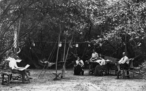 "Black and white photograph postcard of people camping.  Inscription on back reads: ""Dr. Willard, at right, and party at camp where [unable to read name] was the [unable to read word]."""
