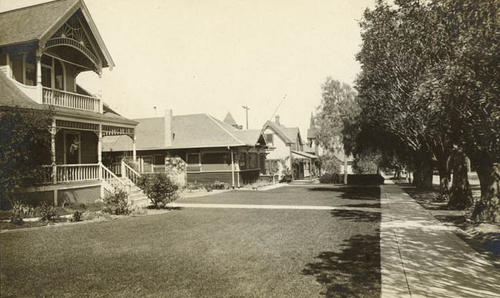 Black and white photograph postcard showing at least three houses.