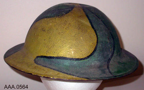 This artifact is a WWI American Army Helmet.  This is a camouflage hat with a leather headband and strap.  The lot number #ZC38 is stamped on the inside. Donor's Remarks:  This had belonged to Grover C. Rutledge.