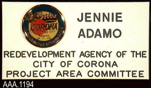 "This artifact is the name badge for Jennie Adamo.  The badge is white with dark blue text and a raised city seal.  The text on the badge reads: ""Jennie Adamo - Redevelopment Agency of the - City of Corona - Project Area Committee."""