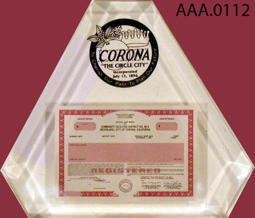 "This artifact is a clear plastic paperweight with a miniture copy of the Community Facilities District, No. 86-2 (Woodlake).  Above this is the City of Corona logo.  It measures 4 3/4"" x 1"" x 4 1/2""."