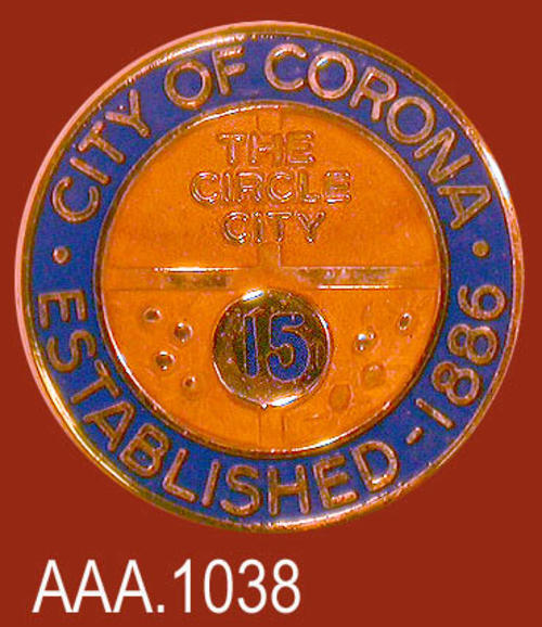 "This artifact is a gold and blue pin to commemorate fifteen years of service.  On the outer blue circle in gold letters is the following text:  CITY OF CORONA - ESTABLISHED 1886.""  In the center of the pin are the words:  ""The Circle City,""  and the numeral, ""15."""