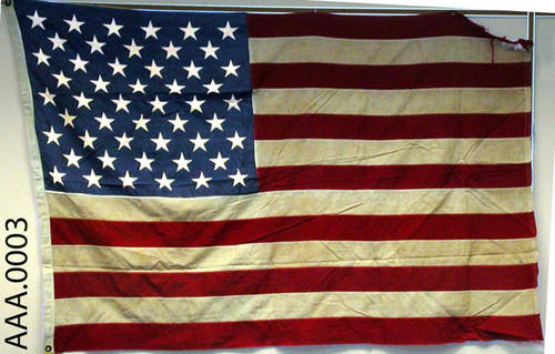This artifact is a fifty-star, American flag (frayed on stripped top corner).  It measures 6' x 4'.  CONDITION:  White stripes are yellowed.
