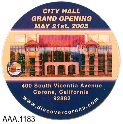 "This artifact collection consists of two, identical,circular, magnetic advertisements for the opening of the new Corona City Hall. The text at the top reads: ""City Hall - Grand Opening - May 21st, 2005.""  Under this text is a photo of the new city hall along with the city logo. The following text is below the photo:  ""400 South Vicentia Ave. - Corona, California - 92882.""  Arched at the base of the magnet is the following text: ""www.discovercorona.com."" This magnet measures 3"" in diameter."