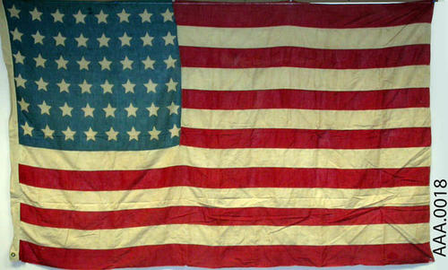 This artifact is an American, forty-eight star, flag. CONDITION:  This flag is in good condition, but faded.