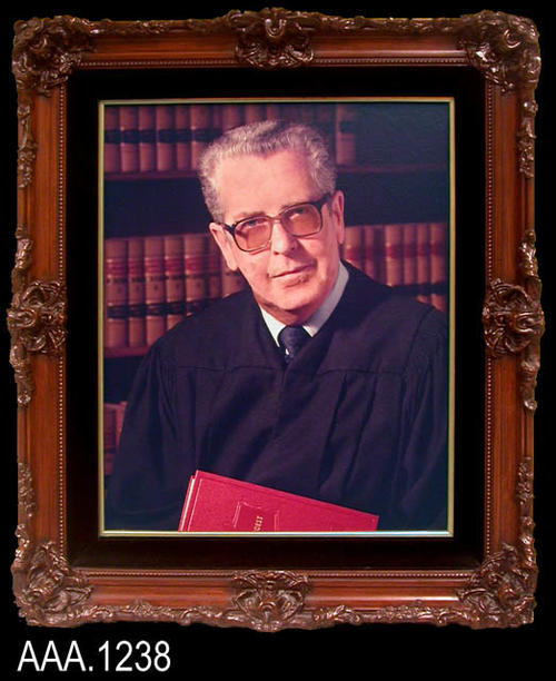 "This artifact is a framed color photograph of the Hon. Michael F. Flynn. It hung on the wall of the Corona Courthouse were he served as judge.  This framed work measures 27 1/4"" x 23"" x 3 1/4"".  Rubber stamped on the back is the following text:  ""Community Photography, 4205 Market St., Suite 2, Riverside, CA."""