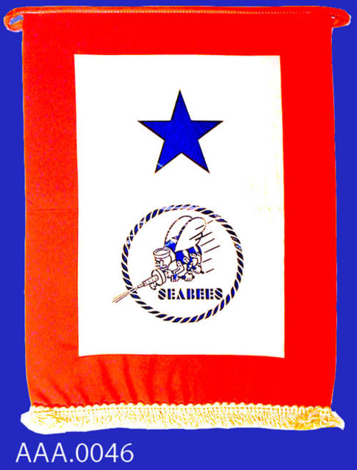 This artifact is a military flag with a red border and a white center.  On the white center there is a blue star and a blue rope circle.  Inside the blue rope circle is a Seabee emblem.