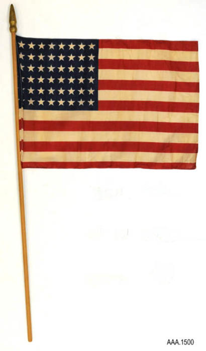 "This artifact is a forty-eight star American Flag on a wooden pole. These flags were found in a safe at the Historic Civic Center.  It is believed that the flags may have been used by the Corona Senior High before the building became the Civic Center. - MEASUREMENTS:  (Flag:  11 1/2 x 16 1/2""), (Pole:  28 1/4"" Height, 3/8"" Diameter).  QUANTITY:  3."