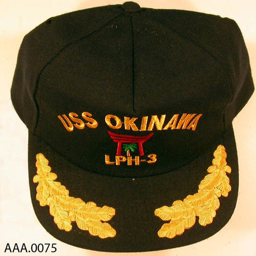 This artifact is a blue, adjustable ball cap with the insignia USS OKINAWA on the front with scrambled eggs on the bill. On the back: Decommissioning Apr. 1962 - Dec. 1992.