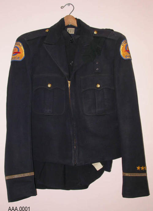 This artifact is a  blue police uniform, shirt, tie, trousers, short jacket with Corona Police Patches on both shoulders.  One stripe (Gold and Blue) and four gold stars are on each sleeve - CONDITION: Good, but needs cleaning.