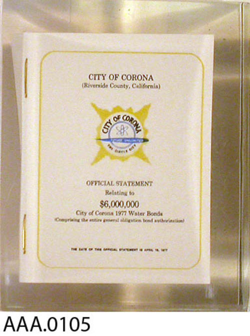 "This artifact is a clear plstic paperweight with a miniture copy of the City of Corona - Official statement relating to the $6,000,000 City of Corona, 1977 Water Bonds.  It measures 2"" x 2"" x 2 1/2""."