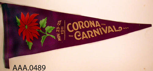 "This artifact is a pennant which measures 28 3/4"" x 15 1/2"".  It is purple with a red poinsettia.  The following text is in white letters:  ""Nov. 23 - 25, 1911 - Corona Carnival."""