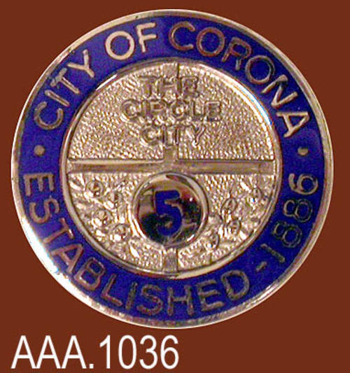 "This artifact collection consists of four identical five year service pins for the City of Corona.  Each pin is blue and silver.  On the outer blue ring is the following text in silver:  ""CITY OF CORONA - ESTABLISHED 1886.""  In the center is the text:  ""The Circle City,"" with a blue numeral ""5"" below in a circle. This pin measures 9/16"" in diameter."