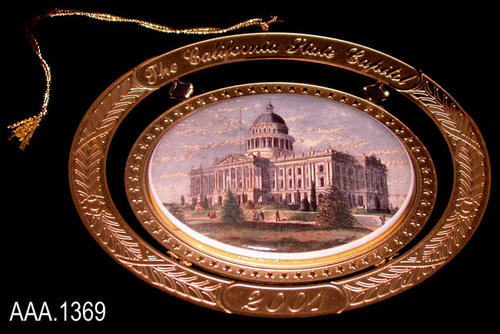 "This artifact is the 2001 Ornament from Governor Gray Davis and First Lady Sharon Davis.  The ornament is oval in shape.  Text at the top of the ornament reads:  ""The California State Capitol.""  Text at the bottom reads:  ""2001.""  In the center of the ornament, replicating scrimshaw,  is an oval piece of plastic with a picture of the California State Capitol Building.  Engraved on the back in cursive text is the following:  "" Governor Gray Davis - and First Lady Sharon Davis - Made in the USA.""  There is an insert that comes with the ornament signed by Governor and Mrs. Davis.  Historical information is printed on the back and is signed by Dr. Kevin Starr, State Librarian of California.  The ornament is boxed in a gold foil box with a black State Seal on the front.  An enclosed metal bar can be attached to the ornament turing it into a stand-alone display piece."