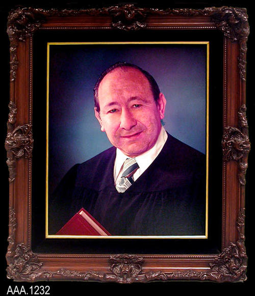 "This artifact is a framed color photograph of the Hon. J. William Mortland.  It hung on the wall of the Corona Courthouse were he served as judge.  This framed work measures 27 1/4"" x 23"" x 3 1/4""."