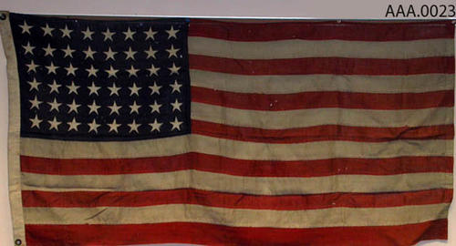 This artifact is a forty-eight star American Flag.  CONDITION:  This flag is in very poor condition. It is dirty and has holes in it.