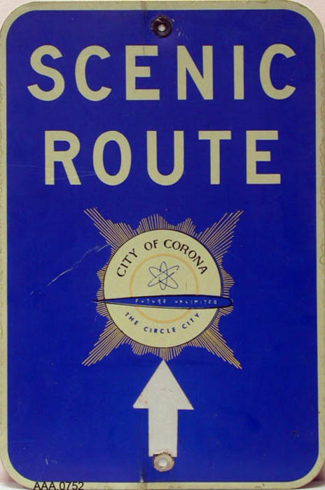 This artifact consists of 2 Scenic Route signs for the City of Corona with the future unlimited logo.  These signs are new and have never been used.  The background of the sign is blue with white, block letters.  There is a gold color in the logo. Donor's Remarks:  This sign was typical of those posted throughout the city after a scenic route  was put together and adopted by the Chanber of Commerce in 1971.