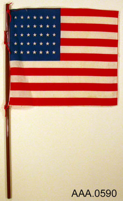 This artifact is a miniature American flag with thirty-five stars on a pole.