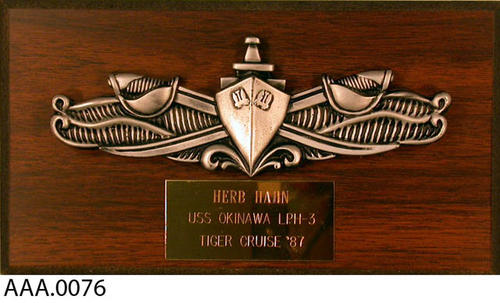 "This artifact is a plaque has a silver surface warfare emblem and a plate with the inscription:  ""Herb Hann - USS OKINAWA LPH-3 - Tiger Cruise."""