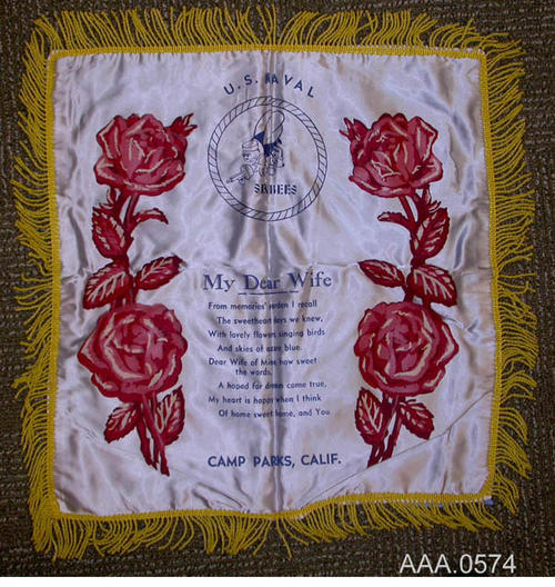 "This artifact is a pillow cover that has a gray-black ground, red roses down each side and a blue See Bee logo.  The words:  ""My Dear Wife,"" a poem, and Camp Parks, Calif. are in gold letters.  There is a 1 3/4"" gold fringe around the outside. Donor's Remarks:  This artifact was owned by Jenny Adamo and belonged to the Rutledge Family."