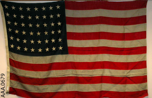 This artifact is a 48 star American Flag.  CONDITION:  There are several holes on the face of this flag.  The white on the flag, especially the stripes, have grayed.
