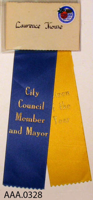 "This artifact is a blue ribbon.  The gold text on the ribbon reads: ""City Council Member and Mayor.""  The text on the yellow ribbon reads, ""Citizen of  The Year."""