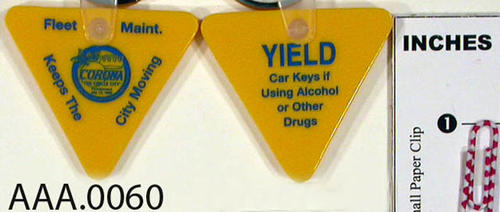 "This artifact is a triangle shaped, yellow rubber, key ring with blue writing.  In the center is the City of Corona emblem and the following wording:  ""Fleet Maint. - Keep This - City Moving.""  The opposite side says, ""Yield Car keys if using alcohol or other drugs.""  QUANTITY:  Four key rings"