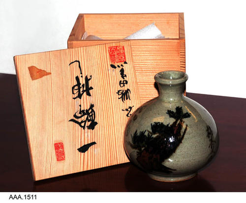 This artifact is a small ceramic vase that comes in a wooden box.  The vase is gray-green with Japanese characters in black.  The lid of the box has Japanese characters in red and black on both sides of the lid.  CONDITION:  New.