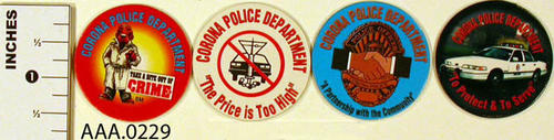 This artifact collection consists of pogs from the Corona Police Department with various logos.