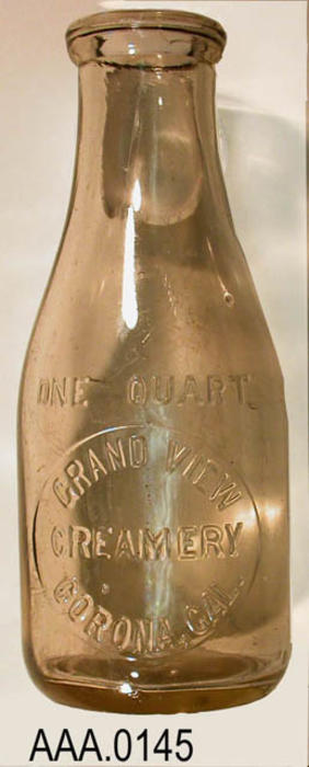This artifact is a one quart, milk bottle from the Grand View Creamery, Corona, California. Donor's Remarks:  This bottle was dug up in the backyard of the house at 3461 Valley View, Norco, California.